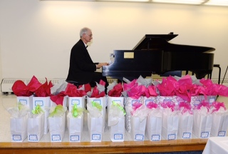 Richard Gagliano playing piano and scholarship gift bags lined up